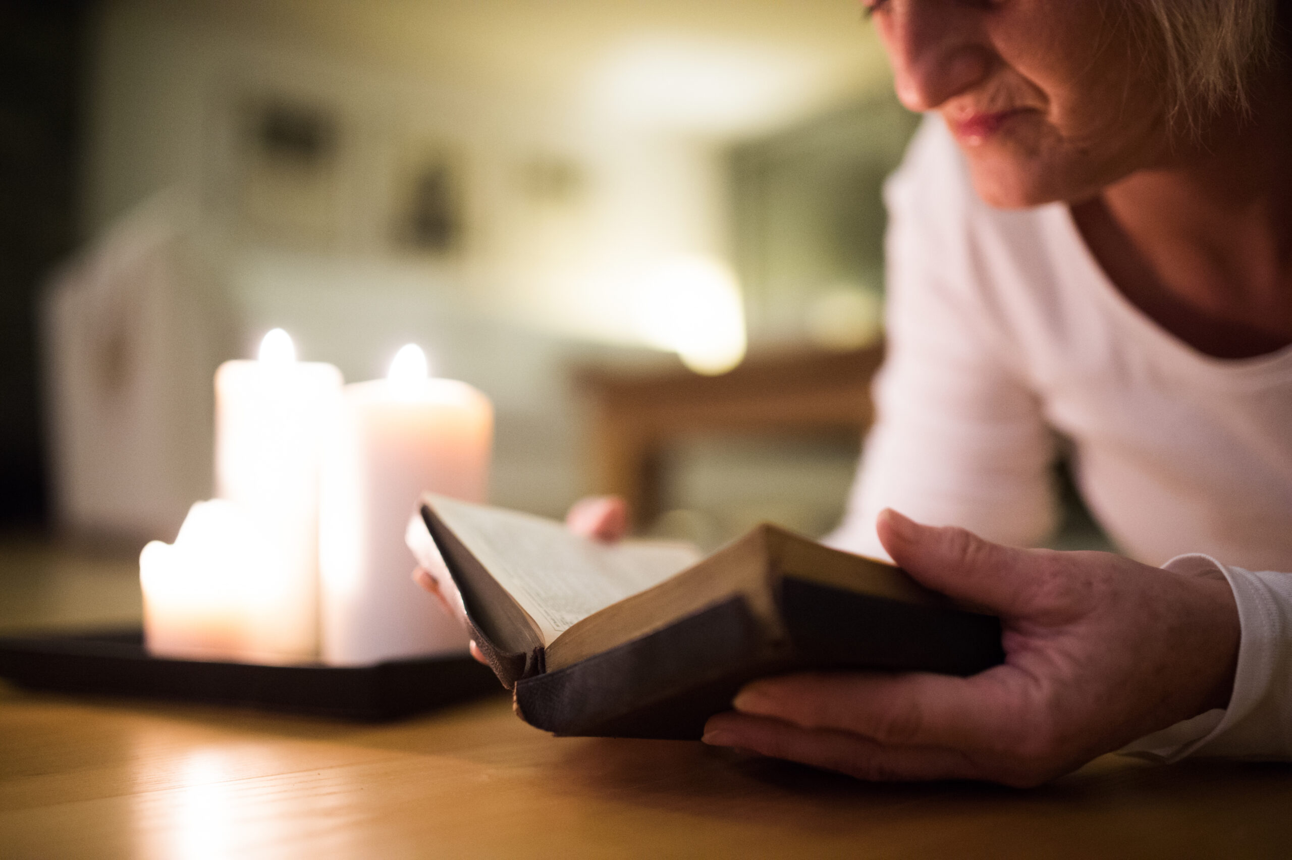 Stock - graphicstock-unrecognizable-woman-lying-on-the-floor-reading-her-bible-burning-candles-next-to-her-close-up_Bdncn_Iz-
